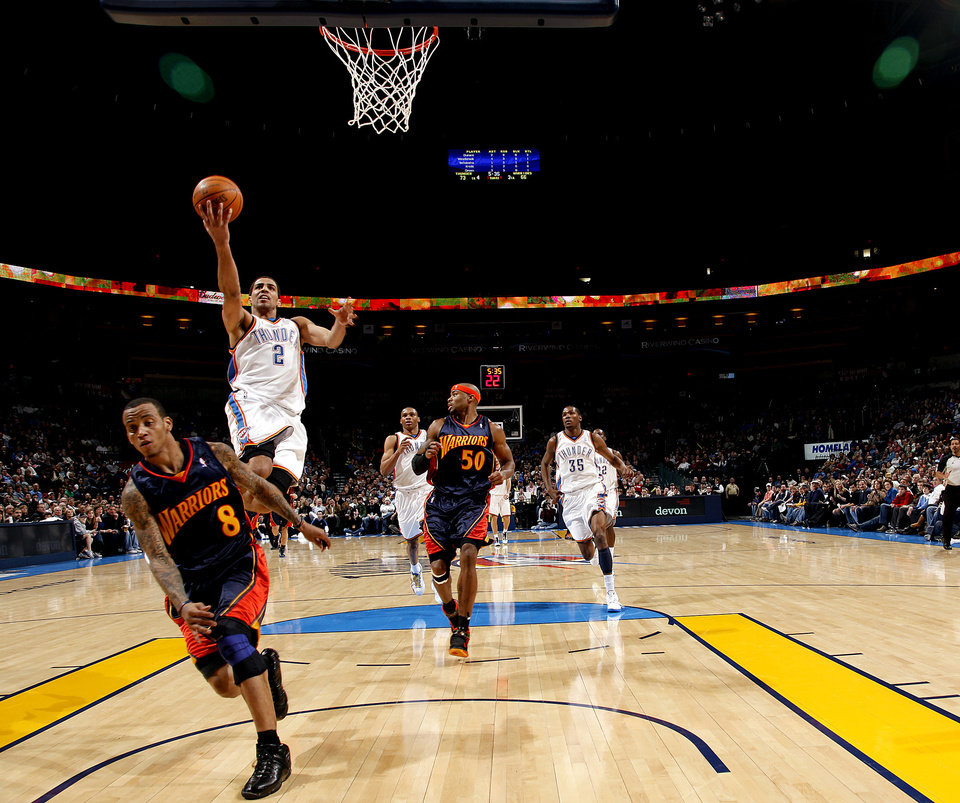Photo - Oklahoma City's Thabo Sefolosha (2) shoots a lay up in  between Golden State defenders Monta Ellis (8) and Corey Maggette (50) during the NBA game between the Oklahoma City Thunder and Golden State Warriors, Sunday, Jan. 31, 2010, at the Ford Center in Oklahoma City. Photo by Sarah Phipps, The Oklahoman