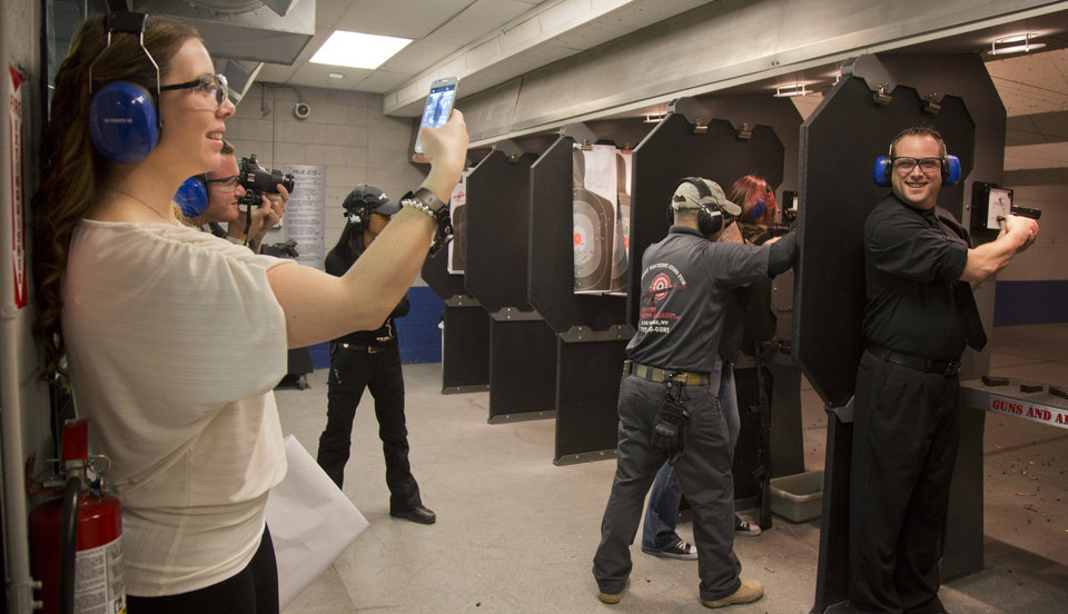 Photo - Tanya Morris, left, takes a photo of her new husband, Ted Morris on the shooting range after getting married at the Guns and Ammo Garage, Thursday, Feb. 14, 2013, in Las Vegas. Never known for its understatement or good taste, Sin City is bucking the national trend of avoiding flippant gun promotions after the Newton, Conn., elementary school shooting. Instead, it is embracing tourists' newfound interest in big guns the only way it knows how: by going all in.  (AP Photo/Julie Jacobson)
