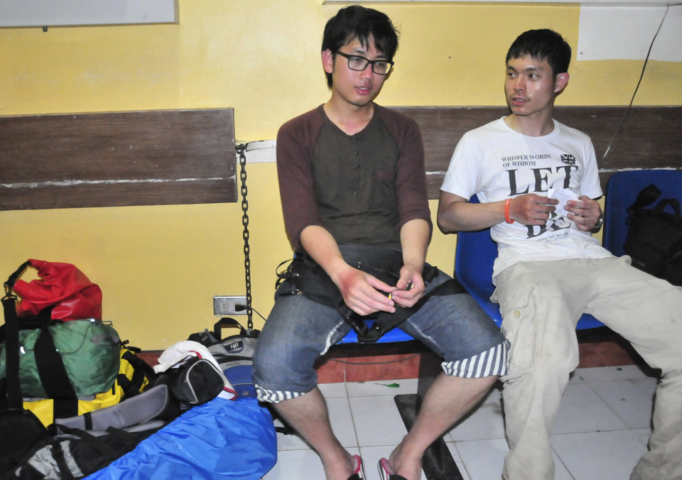 Photo - Thai nationals, Nithi Rvangpisit, left, and Tanut Rvchippiyarak, rest in a hospital in Legazpi city with their mountain climbing gear after surviving a steam-driven explosion of Mayon volcano, one of the Philippines' most active volcanoes, Tuesday, May 7, 2013 in Albay province, about 450 kilometers (285 Miles) southeast of Manila, Philippines. Mayon volcano rumbled to life Tuesday, spewing room-sized rocks toward nearly 30 surprised climbers, killing five and injuring others that had to be fetched with rescue helicopters and rope. (AP Photo/Nelson Salting)
