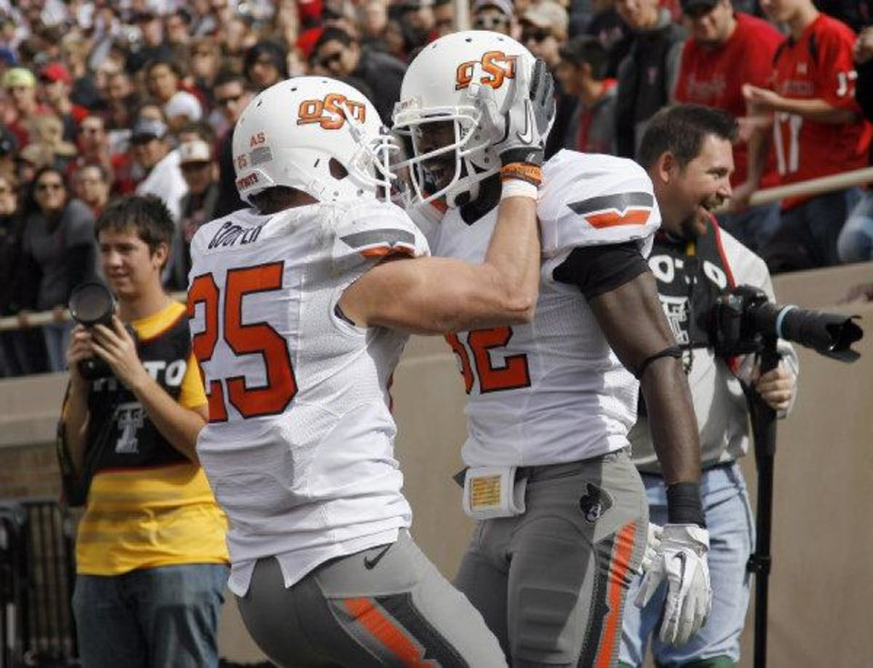 Oklahoma State's Josh Cooper (25) and Isaiah Anderson (82) celebrate a touchdown during a NCCA football game between Texas Tech University (TTU) and Oklahoma State University (OSU) at Jones AT&T Stadium in Lubbock, Texas, Saturday, Nov. 12, 2011. Photo by Sarah Phipps, The Oklahoman <strong>SARAH PHIPPS</strong>