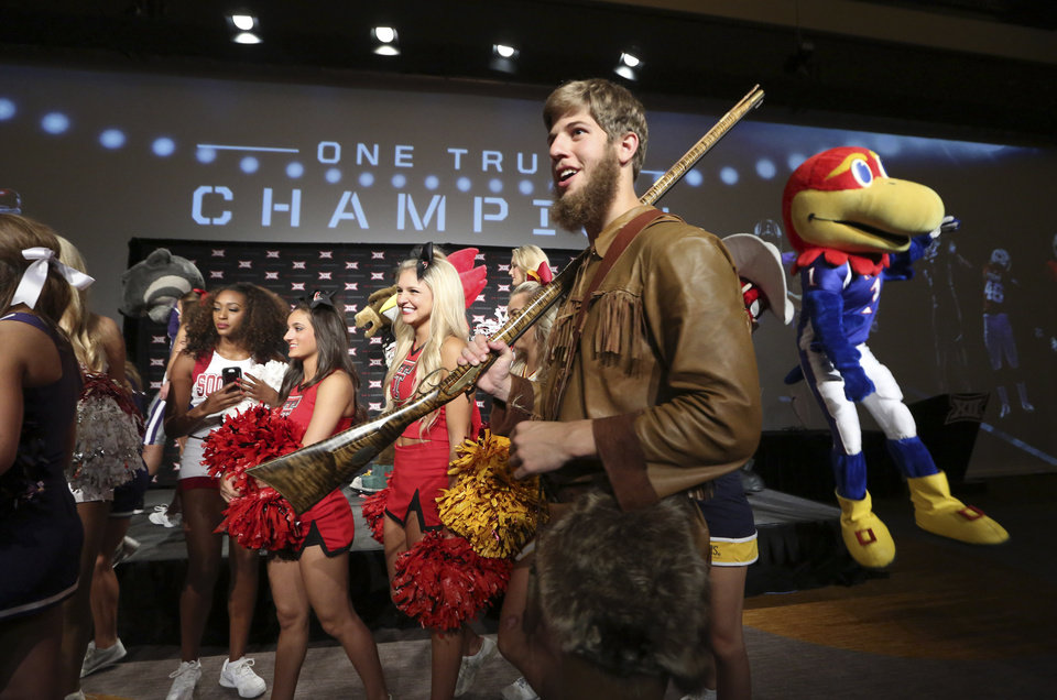 Photo - Michael Garcia, dressed as West Virginia's mountaineer mascot, caries a musket after posing for a photo with cheerleaders and mascots at the Big 12 Conference NCAA college football media days in Dallas, Tuesday, July 22, 2014. (AP Photo)