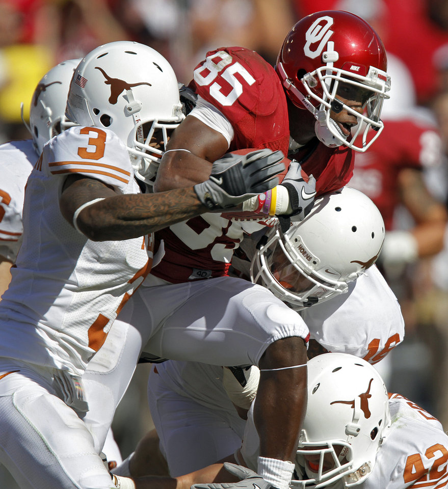 Oklahoma's Ryan Broyles (85) is brought down by Texas' Curtis Brown (3) of the Red River Rivalry college football game between the University of Oklahoma Sooners (OU) and the University of Texas Longhorns (UT) at the Cotton Bowl on Saturday, Oct. 2, 2010, in Dallas, Texas.   Photo by Chris Landsberger, The Oklahoman