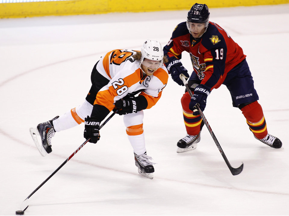 Photo - Philadelphia Flyers center Claude Giroux (28) carries the puck as Florida Panthers right wing Scottie Upshall (19) defends during the first period of an NHL hockey game in Sunrise, Fla., on Tuesday, April 8, 2014. (AP Photo/Terry Renna)