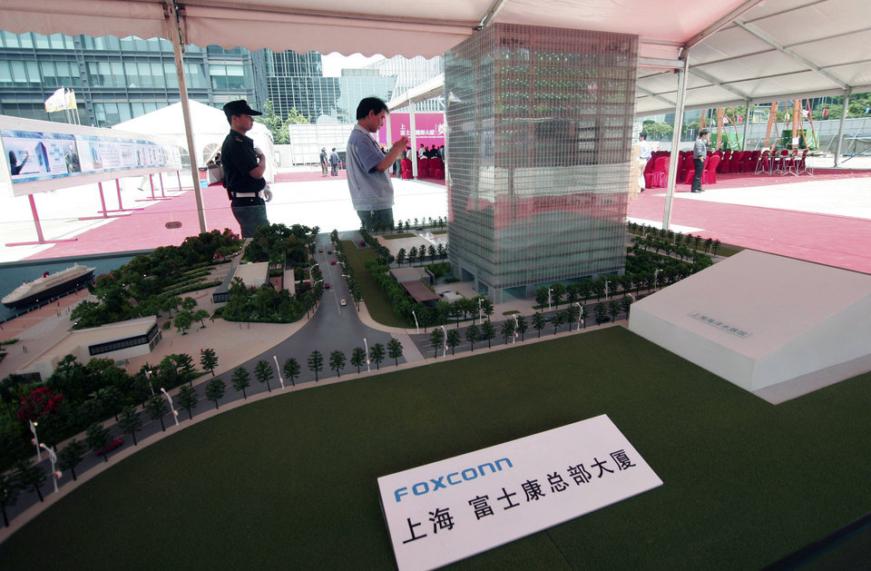 Photo -   FILE-In this Thursday, May 10, 2012, file photo, Chinese men walk near a scale model of the Shanghai headquarters for the Foxconn Technology Group displayed at the groundbreaking ceremony in Shanghai, China. The company that makes Apple's iPhones suspended production at a factory in China on Monday, Sept. 24, 2012, after a brawl by as many as 2,000 employees at a dormitory injured 40 people. The fight, the cause of which was under investigation, erupted Sunday night at a privately managed dormitory near a Foxconn Technology Group factory in the northern city of Taiyuan, the company and Chinese police said. (AP Photo/File)