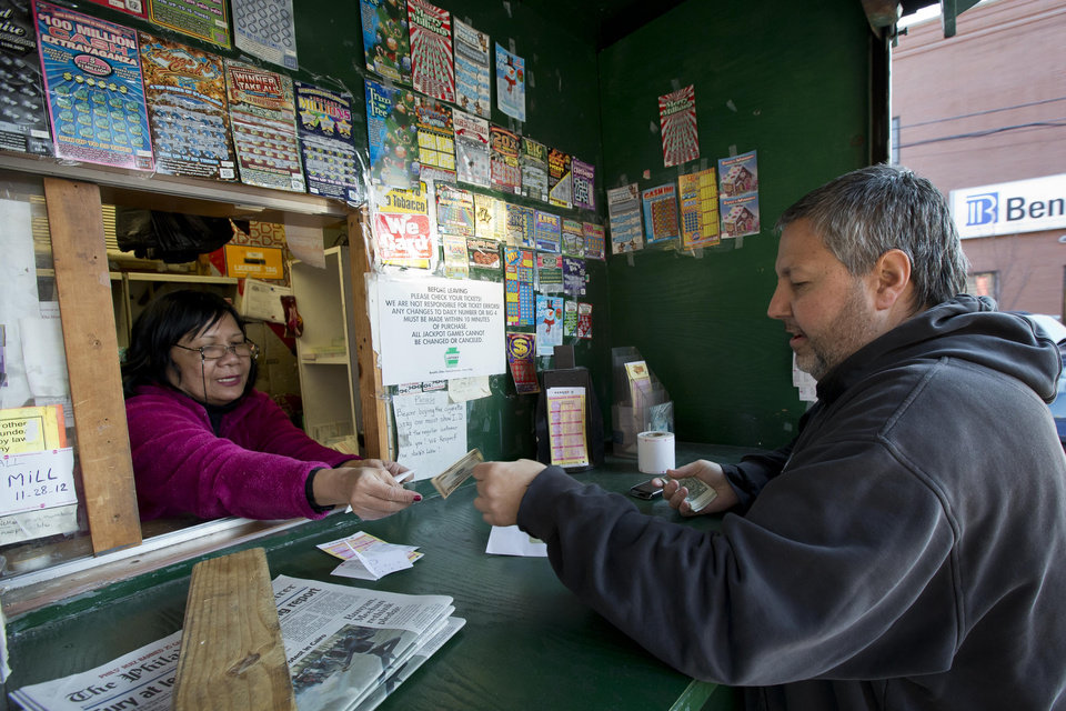 Photo - Norn Phneo sells Powerball tickets to Billy Fulginiti, of Philadelphia for himself and his coworkers, Wednesday, Nov. 28, 2012, in Philadelphia. (AP Photo/Matt Rourke)