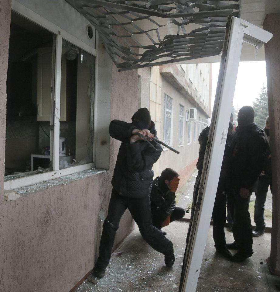 Photo - A Pro-Russian man attacks a police station in the eastern Ukrainian town of Horlivka Monday, April 14, 2014.  Several government buildings have fallen to mobs of Moscow loyalists in recent days as unrest spreads across the east of the country.  (AP Photo/Efrem Lukatsky)