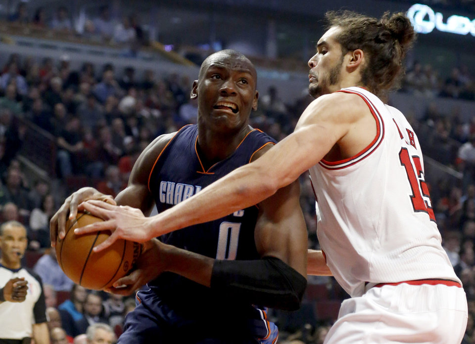 Chicago Bulls center Joakim Noah (13) pressures Charlotte Bobcats forward Bismack Biyombo during the first half of an NBA basketball game, Monday, Jan. 28, 2013, in Chicago. (AP Photo/Charles Rex Arbogast)