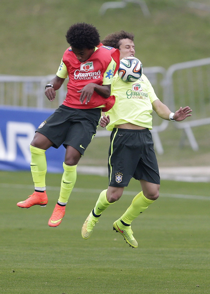 Photo - Brazil's David Luiz, right, and Willian practice during a training session of the Brazilian national soccer team at the Granja Comary training center in Teresopolis, Brazil, Monday, June 9, 2014. Brazil play in group A of the 2014 soccer World Cup. (AP Photo/Andre Penner)