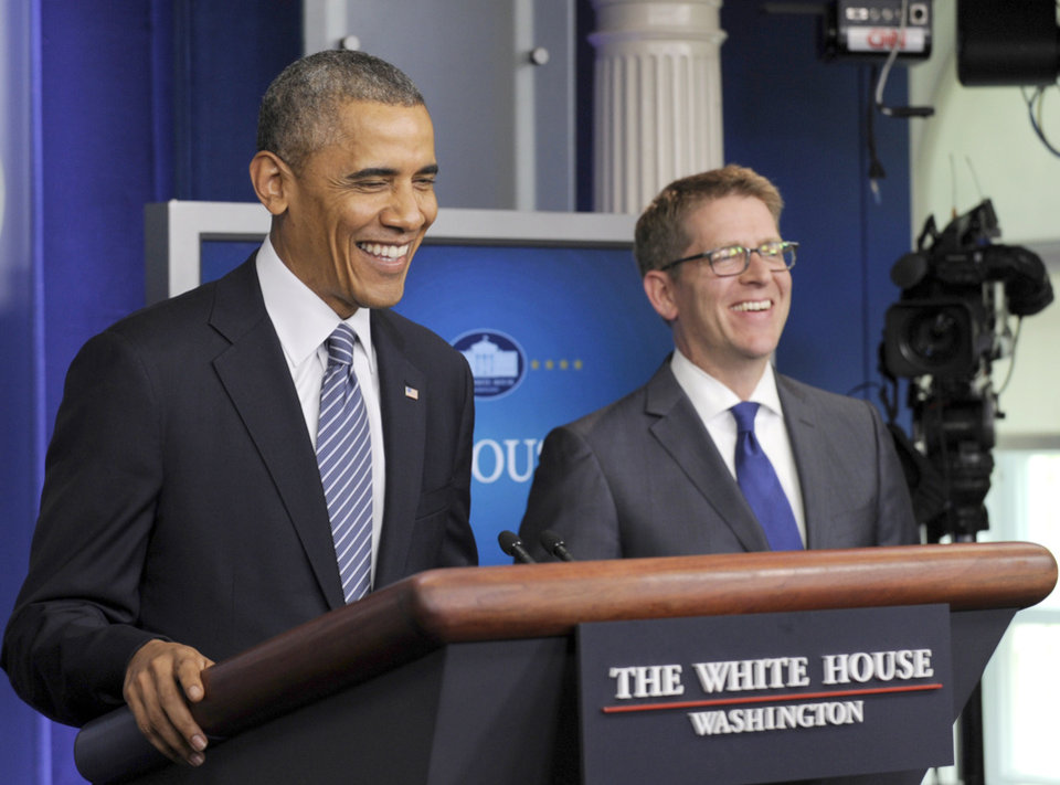 Photo - President Barack Obama shares a laugh as he makes a surprise visit into the Brady Press Briefing Room in Washington, Friday, May 30, 2104, to announce that White House press secretary Jay Carney, right, will be stepping down later next month. The president announced Carney's departure in a surprise appearance at in the White House press briefing room Friday. He said principal deputy press secretary Josh Earnest will take over the job. (AP Photo/Susan Walsh)