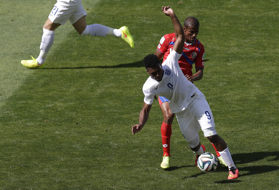 Photo - England's Daniel Sturridge fights for the ball with Costa Rica's Roy Miller during the group D World Cup soccer match between Costa Rica and England at the Mineirao Stadium in Belo Horizonte, Brazil, Tuesday, June 24, 2014. (AP Photo/Michael Sohn)