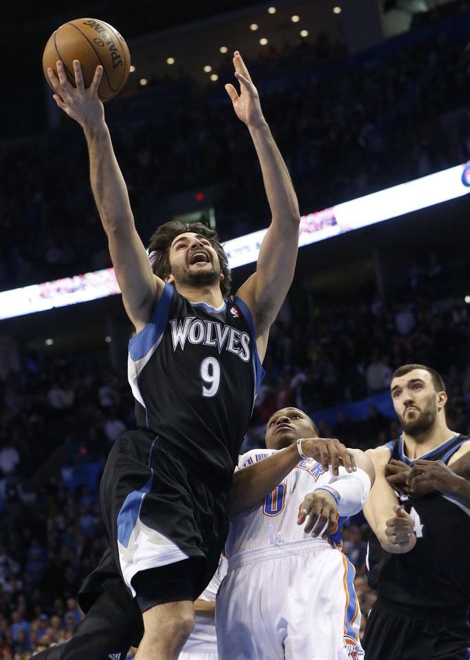 Minnesota Timberwolves guard Ricky Rubio (9) shoots in front of Oklahoma City Thunder guard Russell Westbrook (0) and Timberwolves' Nikola Pekovic, right, in the first quarter of an NBA basketball game in Oklahoma City, Friday, Feb. 22, 2013. (AP Photo/Sue Ogrocki)