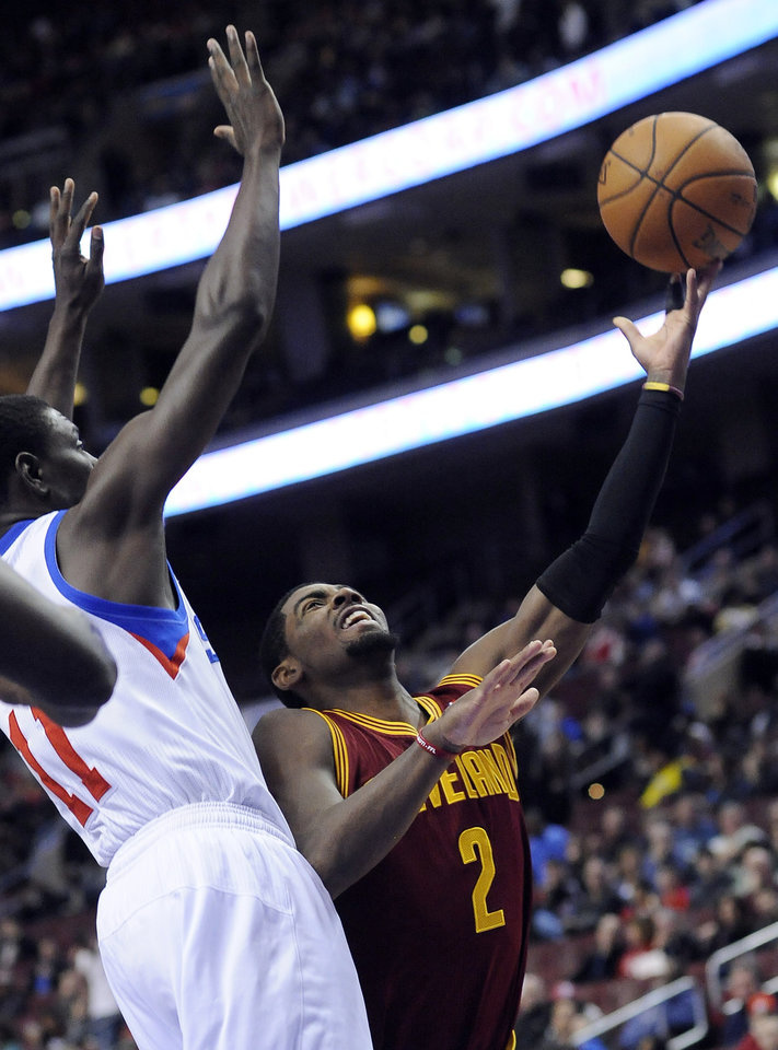 Philadelphia 76ers' Jrue Holiday (11) fouls Cleveland Cavaliers' Kyrie Irving (2) during the first half of an NBA basketball game on Sunday, Nov. 18, 2012, in Philadelphia. (AP Photo/Michael Perez)