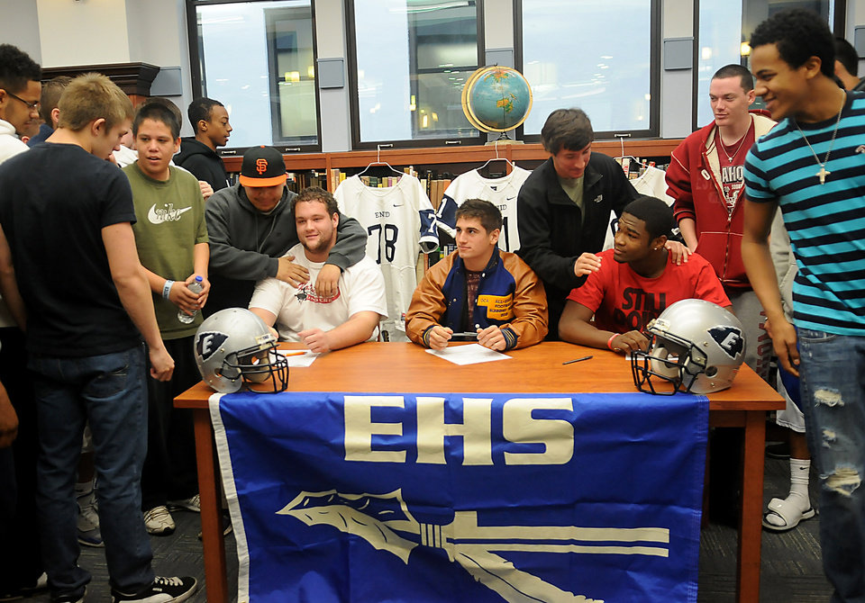 Photo - Enid High School Plainsmen, seated from elft, Logan Miller, Seth Handley and Lance Smith, receive congratulations from their teammates during national signing day at the EHS Library, Wednesday, Feb. 6, 2013, in Enid, Okla. (AP Photo/Enid News and Eagle, Bonnie Vculek)