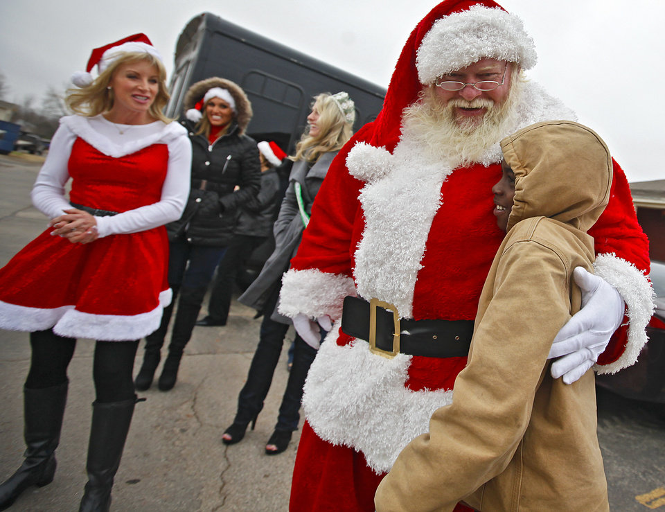 """CHILD / CHILDREN / KIDS: Terion Ellison, 10, gets a hug from Santa Claus, who stopped by the Heritage Pointe Apartments to hand out gifts to kids that reside at the apartments in Oklahoma City, Okla. on Thursday, Dec. 22, 2011. Dr. Harvey Jenkins and Kyle Guffey, two Oklahoma City businessmen organized """"Toys in the Hood,"""" a program through which local businesses offer discounts in exchange for toy donations.  Photo by Chris Landsberger, The Oklahoman"""