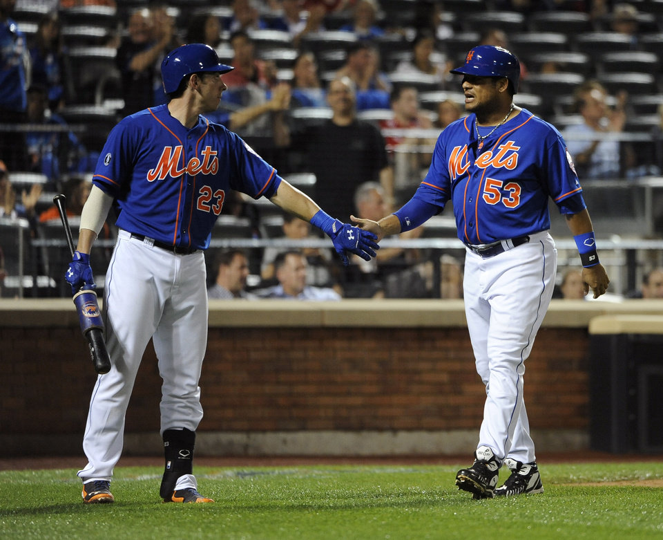 Photo - New York Mets' Taylor Teagarden (23) greets Bobby Abreu (53) at home plate after Abreu scored on a double by Lucas Duda off of San Diego Padres starting pitcher Andrew Cashner in the fourth inning of a baseball game at Citi Field on Friday, June 13, 2014, in New York. (AP Photo/Kathy Kmonicek)