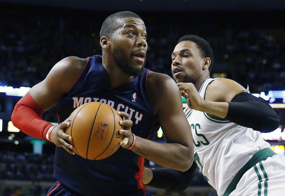 Photo - Detroit Pistons' Greg Monroe, left, looks to shoot past Boston Celtics' Jared Sullinger, right, in the first quarter of an NBA basketball game in Boston, Sunday, March 9, 2014. (AP Photo/Michael Dwyer)