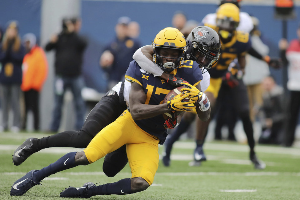 Photo - West Virginia's Sam Jones (13) is tackled at the one yard line by Oklahoma State's Braydon Johnson (8) during the first half of an NCAA college football game in Morgantown, W.Va., on Saturday, Nov. 23, 2019. [AP Photo/Chris Jackson]