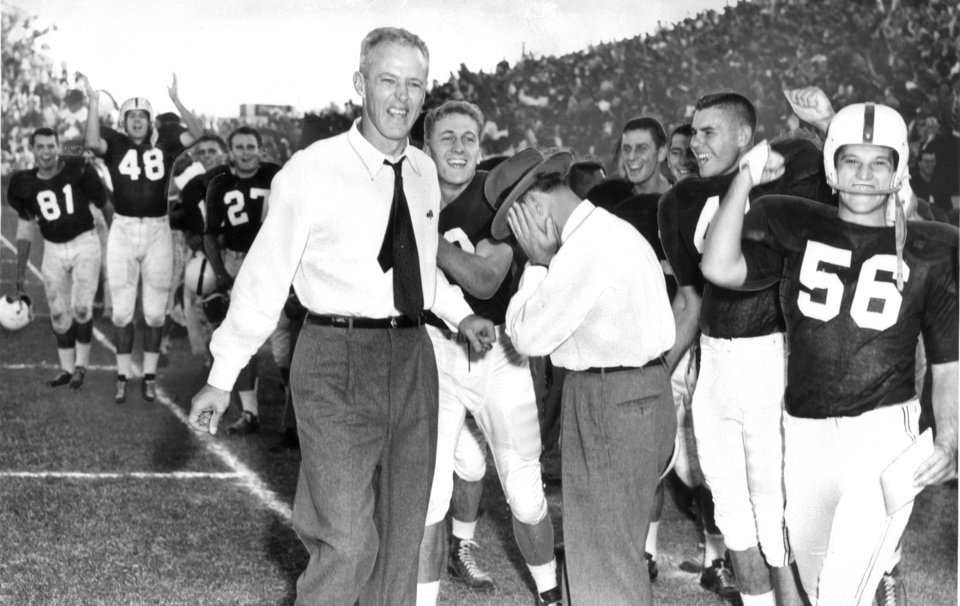There is jubilation on the OU bench as the Sooners score their final touchdown in a 56-21 rout of Colorado in 1955. Coach Bud Wilkinson leads the cheering while line coach Gomer Jones appears to be weeping from joy. Dale DePue pats Wilkinson's back.  Identified players are Bob Timberlake (81), Gerald McPhail (48), Delbert Long (27), Henry Broyles (56). Photo from The Oklahoman Archives