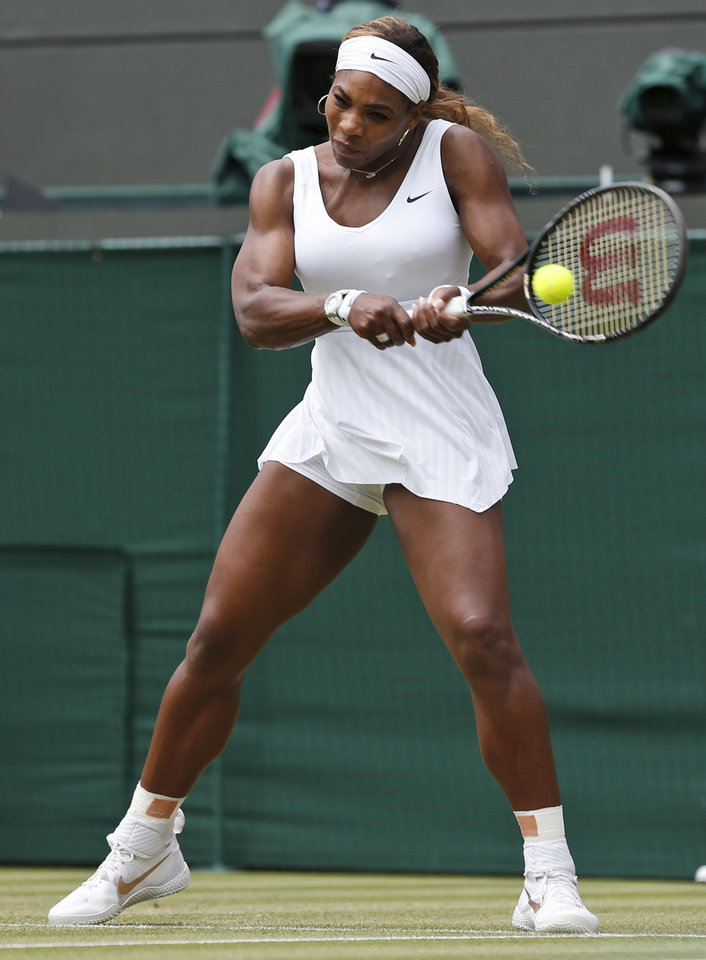 Photo - Serena Williams of U.S. plays a return to Chanelle Scheepers of South Africa during their women's singles match at the All England Lawn Tennis Championships in Wimbledon, London, Thursday, June 26, 2014. (AP Photo/Ben Curtis)