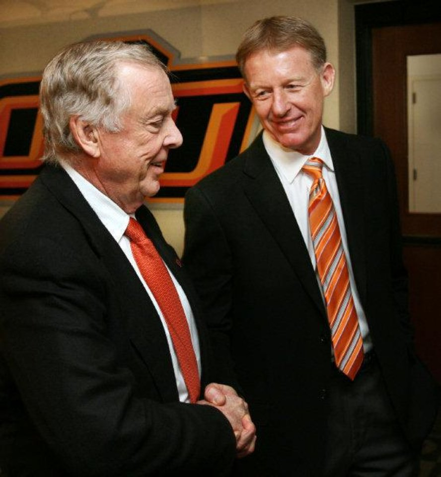 Photo - Boone Pickens (left) is congratulated by athletic director Mike Holder after the announcement of Picken's gift of $165 million to Oklahoma State University's athletic department in Stillwater, Oklahoma on Tuesday, January 10, 2006. by Steve Sisney/The Oklahoman  STEVE SISNEY