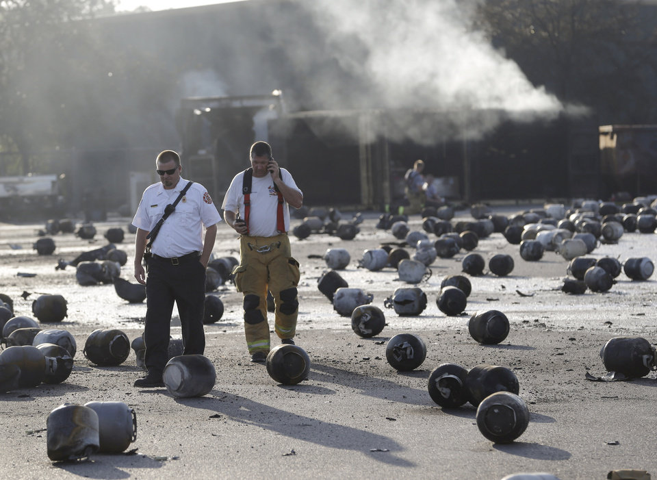 Photo - Firefighters walk through an area of exploded propane cylinders in the aftermath of an explosion and fire at a propane gas company, Tuesday, July 30, 2013, in Tavares, Fla. Eight people were injured, with at least three in critical condition. John Herrell of the Lake County Sheriff's Office said early Tuesday there were no fatalities despite massive blasts that ripped through the Blue Rhino propane plant late Monday night. (AP Photo/John Raoux)