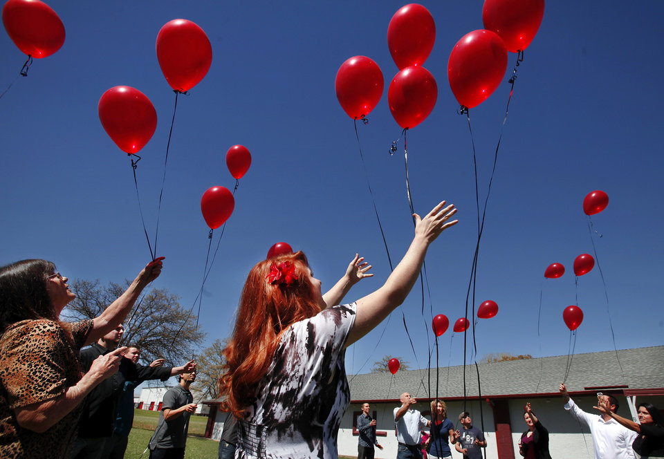 Photo - Friends of Daniel Maxedon, including his girlfriend, Andrea Newcomb, 21, center, release 25 red balloons into the sky at the end of a memorial service for  Maxedon. Nearly two dozen friends and co-workers of Daniel Lewis Maxedon gathered at an Elks Lodge in Midwest City Saturday afternoon, March 24, 2012, to recall and celebrate the life of this young man whose life ended tragically earlier this month.  Maxedon died in Colorado on March 6, having remained  in a coma caused by a severe  head injury sustained when he was assaulted outside a Bricktown bar last November.  The ceremony ended with each person holding red balloons and releasing  25  balloons into the clear blue sky, each balloon representing a year of Maxedon's life. Photo by Jim Beckel, The Oklahoman