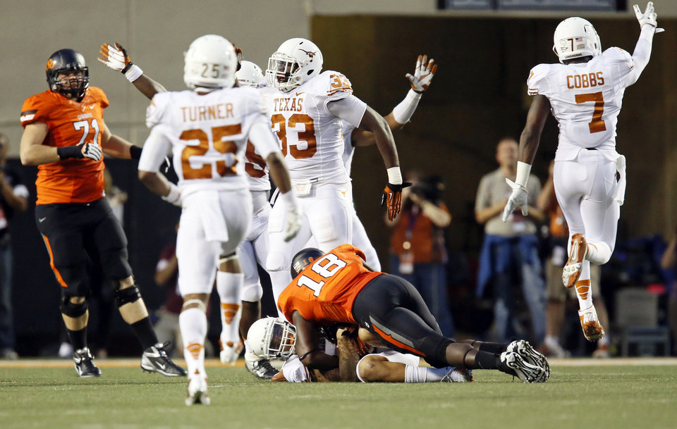 Texas players celebrate an interception by Kenny Vaccaro (4) of a pass intended for OSU's Blake Jackson (18) in the first quarter during a college football game between Oklahoma State University (OSU) and the University of Texas (UT) at Boone Pickens Stadium in Stillwater, Okla., Saturday, Sept. 29, 2012. Photo by Nate Billings, The Oklahoman