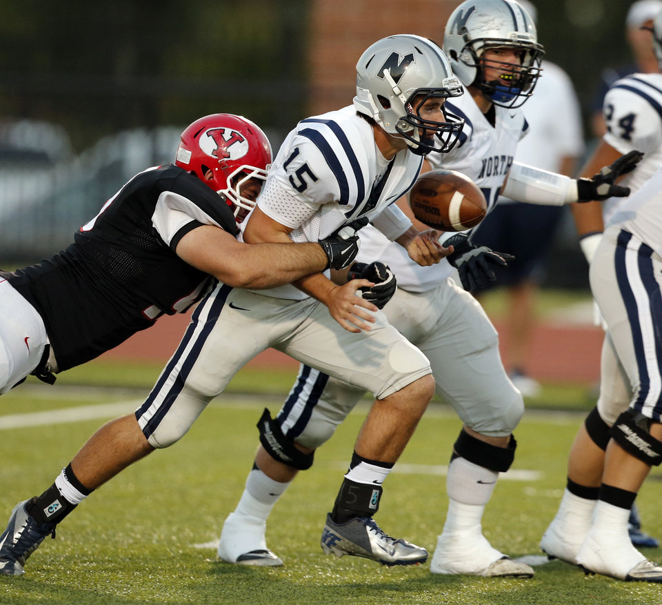 Photo - Yukon's Clint Adams knocks the ball from Edmond North's Stephen McClernon in the first quarter as the Millers play the Huskies play the Millers in high school football on Thursday, Oct. 10, 2013, in Yukon Okla. Photo by Steve Sisney, The Oklahoman