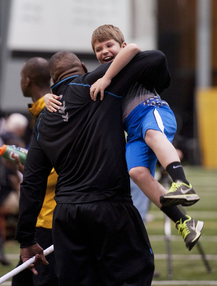 Photo - Missouri defensive lineman Michael Sam, left, picks up Andrew Hill as he greets him during pro day for NFL football representatives Thursday, March 20, 2014, in Columbia, Mo. Hill is the son of associate head coach Andy Hill. (AP Photo/L.G. Patterson)