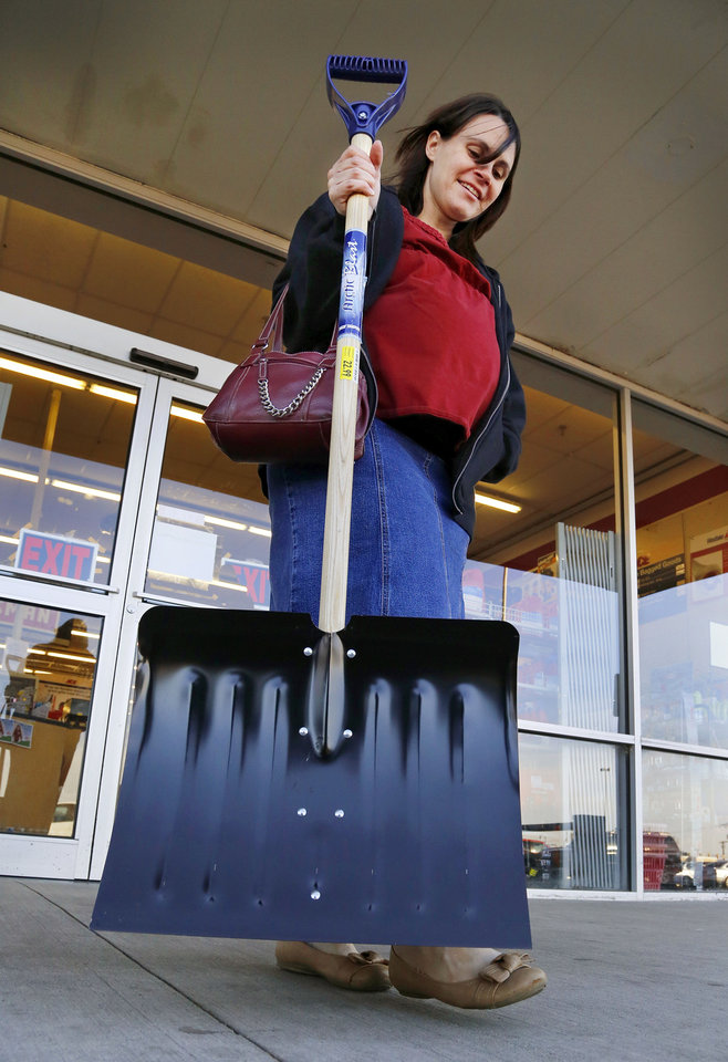 Photo - Tabitha Burgett carries the snow shovel she just purchased to her van in the parking lot of the Westlake Ace Hardware store at SW 44 and Western on Wednesday afternoon, Dec. 4, 2013. Burgett said the shovel was a top priority on her list as she and her husband prepared for an approaching winter storm. She and her husband had talked about the need to buy a snow shovel for a number of weeks but neither had made the purchase.  She said in addition to her trip to the hardware store, she was making a stop at the grocery store.  She and her husband and their five children live in south Oklahoma City. Burgett said when the winter weather arrives, her family will most likely just stay inside their home where it will be cozy and warm.  Jim Robinson, a manager at the store, said a number of customers have purchased shovels and scrapers, but he reported even higher sales of tube sand and ice melt. Photo by Jim Beckel, The Oklahoman