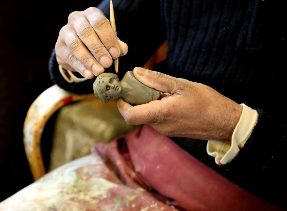 Photo - This May 2, 2014 photo shows a craftsman in the Di Virgilio workshop working on a figurine for a Nativity scene in Naples, Italy. The workshop is located on