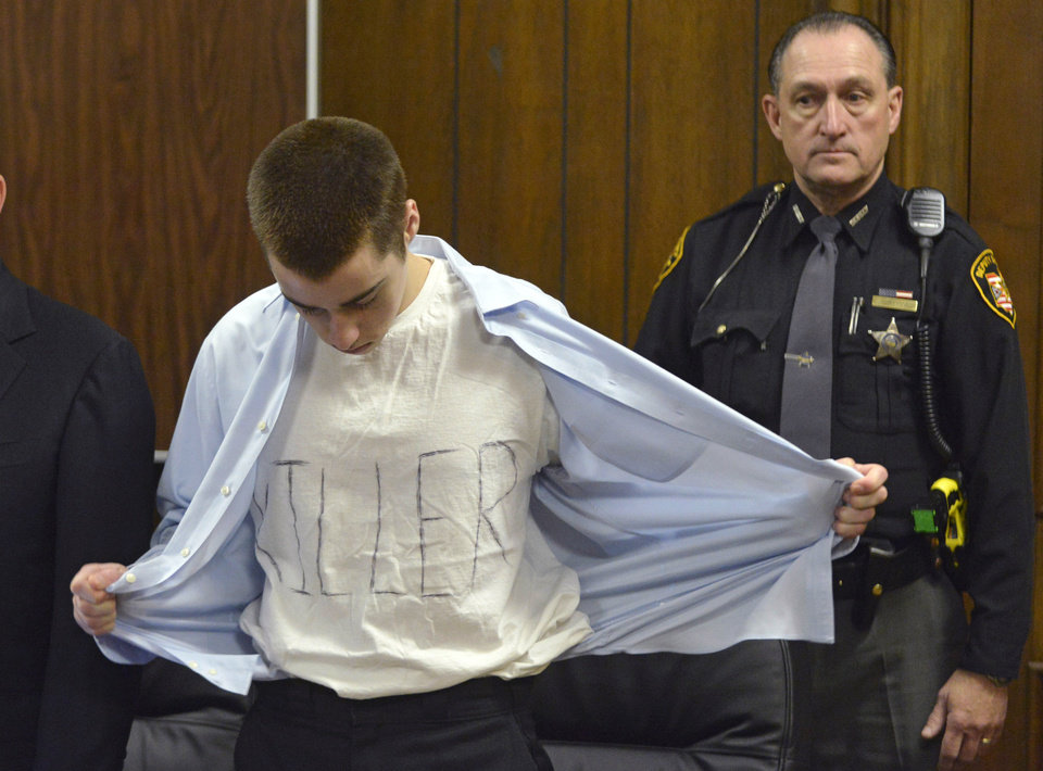 Photo - T.J. Lane unbuttons his shirt during sentencing Tuesday, March 19, 2013, in Chardon, Ohio.  Lane, was given three lifetime prison sentences without the possibility of parole Tuesday for opening fire last year in a high school cafeteria in a rampage that left three students dead and three others wounded.  Lane, 18, had pleaded guilty last month to shooting at students in February 2012 at Chardon High School, east of Cleveland. Investigators have said he admitted to the shooting but said he didn't know why he did it. Before the case went to adult court last year, a juvenile court judge ruled that Lane was mentally competent to stand trial despite evidence he suffers from hallucinations, psychosis and fantasies. (AP Photo/The News-Herald, Duncan Scott, Pool)