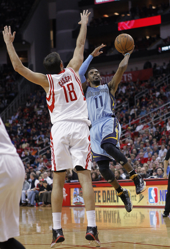 Photo - Memphis Grizzlies guard Mike Conley (11) drives to the basket as Houston Rockets' Omri Casspi (18) defends during the first half of an NBA basketball game Thursday, Dec. 26, 2013, in Houston. (AP Photo/Bob Levey)