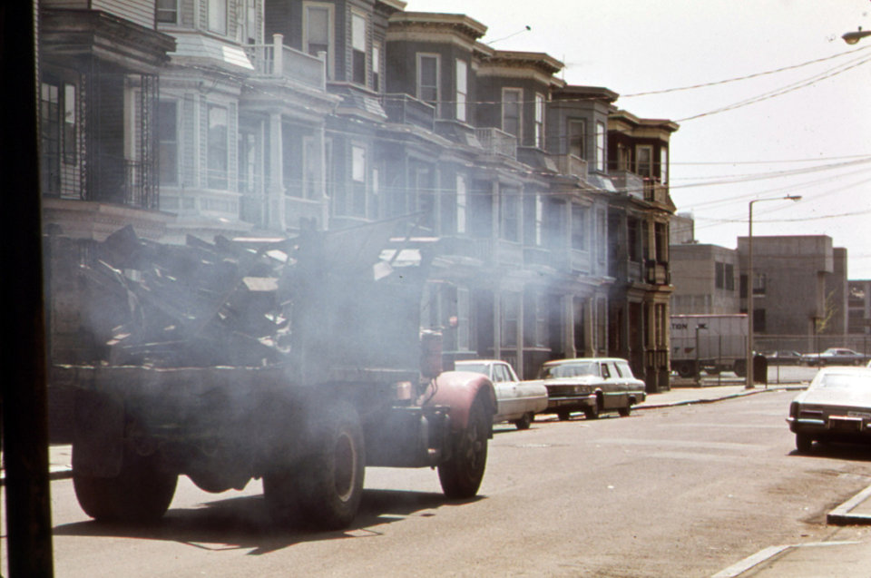 "This photo, taken between 1972 and 1977 and released by the U.S. National Archives, shows a truck moving through a residential neighborhood on Lovell Street, adjacent to Logan Airport in Boston. The street ends at the Wood Island Transit Station near construction on a building to be leased to the food preparation business for one of the airlines. The image was taken for new Environmental Protection Agency's ""Documerica"" program, 1972-1977, to document subjects of environmental concern. (AP Photo/U.S. National Archives, Michael Philip Manheim)"