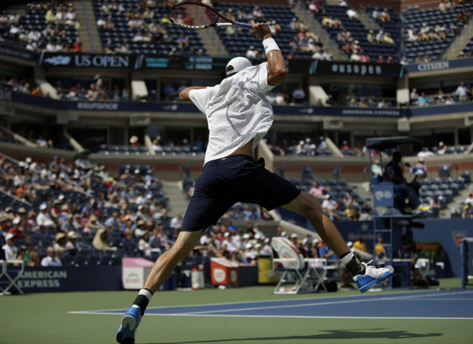 Photo - John Isner, of the United States, follows through on a return against Marcos Giron, of the United States, during the opening round of the 2014 U.S. Open tennis tournament, Tuesday, Aug. 26, 2014, in New York. (AP Photo/Kathy Willens)