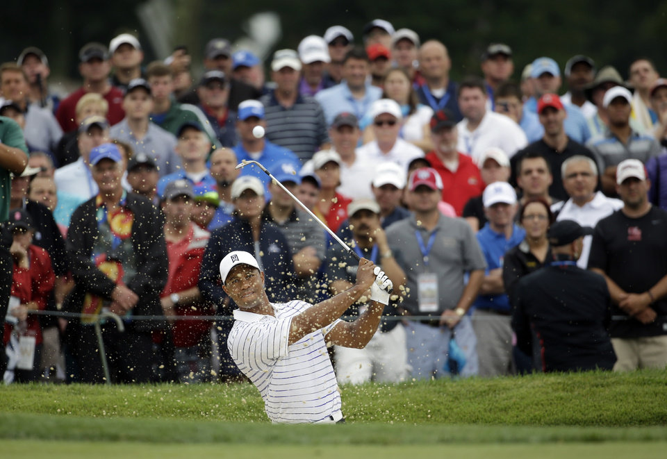 Photo - Tiger Woods hits out of the bunker on the first hole during the second round of the PGA Championship golf tournament at Valhalla Golf Club on Friday, Aug. 8, 2014, in Louisville, Ky. (AP Photo/Jeff Roberson)
