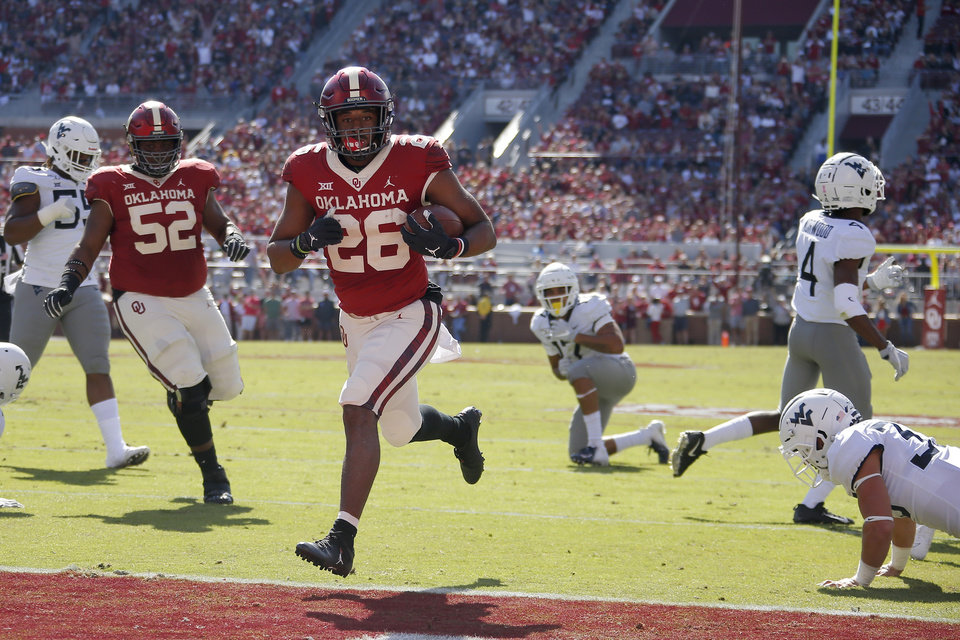 Photo - Oklahoma's Kennedy Brooks (26) scores a touchdown during a college football game between the University of Oklahoma Sooners (OU) and the West Virginia Mountaineers at Gaylord Family-Oklahoma Memorial Stadium in Norman, Okla, Saturday, Oct. 19, 2019. [Bryan Terry/The Oklahoman]