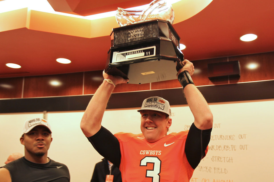 Photo - Brandon Weeden holds the Big 12 championship trophy aloft after the presentation in the Cowboys locker room Saturday Dec. 3, 2011. The Cowboys snapped an eight-game losing streak and won their first outright conference title since 1948 in the three-team Missouri Valley. (AP Photo/Oklahoma State University)