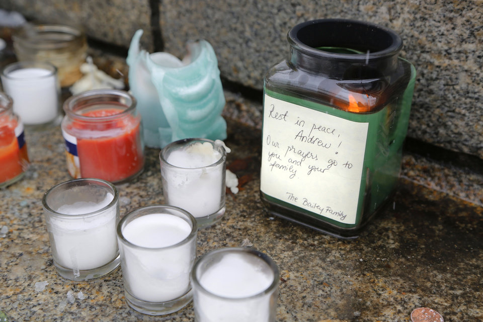 Photo - Candles, several still burning, along with flowers are placed on the steps of Hovde Hall in memorial to slain engineering student Andrew Boldt Wednesday, Jan.  22, 2014, on the campus of Purdue University in West Lafayette, Ind. Boldt was shot and killed Tuesday at the Electrical Engineering building.   Cody Cousins, a student, has been charged in the shooting.     (AP Photo/Journal & Courier, John Terhune)