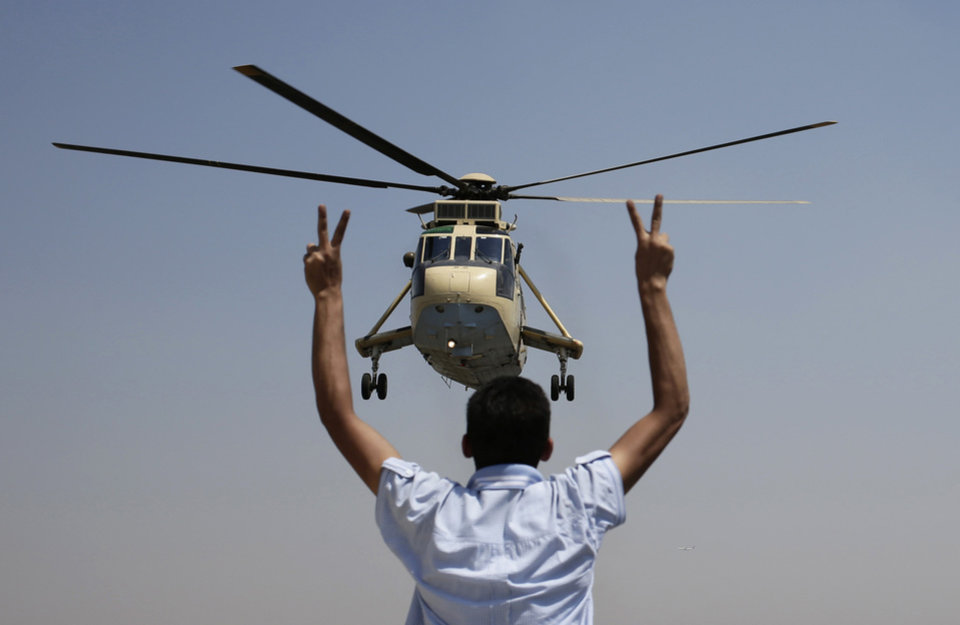 Photo - A man flashes victory signs at an Egyptian military helicopter as it flies over the presidential palace in Cairo, Egypt, Friday, July 26, 2013. Political allies of Egypt's military lined up behind its call for huge rallies Friday to show support for the country's top general, Abdel-Fattah el-Sissi, pushing toward a collision with Islamist opponents demanding the return of Mohammed Morsi, the nation's ousted president. (AP Photo/Hassan Ammar)