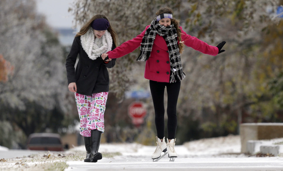 Photo - Jane Giles, 15, right, gets some help from her sister Sarah Giles 17, as she skates on an icy sidewalk Friday, Dec. 6, 2013, in Richardson, Texas. The National Weather Service issued winter storm and ice warnings through much of Friday for parts of Texas, Oklahoma, Arkansas, Mississippi, Missouri, Illinois, Indiana and Tennessee. (AP Photo/LM Otero)