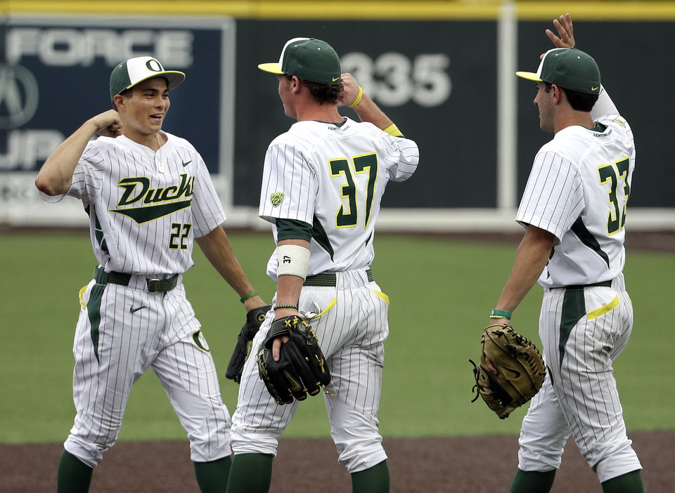 Photo - Oregon players Austin Grebeck (22), Mitchell Tolman (37) and A.J. Balta (33) celebrate their 18-1 win over Clemson in an NCAA college baseball regional tournament game on Friday, May 30, 2014, in Nashville, Tenn. (AP Photo/Mark Humphrey)