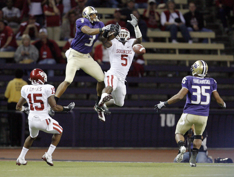 Photo - OU's Nic Harris (5) deflects a pass intended for UW's Alvin Logan (3) into the hands of Brandon Yakaboski for a Husky touchdown as OU's Dominique Franks (15) looks on in the fourth quarter during the college football game between Oklahoma and Washington at Husky Stadium in Seattle, Wash., Saturday, September 13, 2008. OU beat UW, 55-14. BY NATE BILLINGS, THE OKLAHOMAN