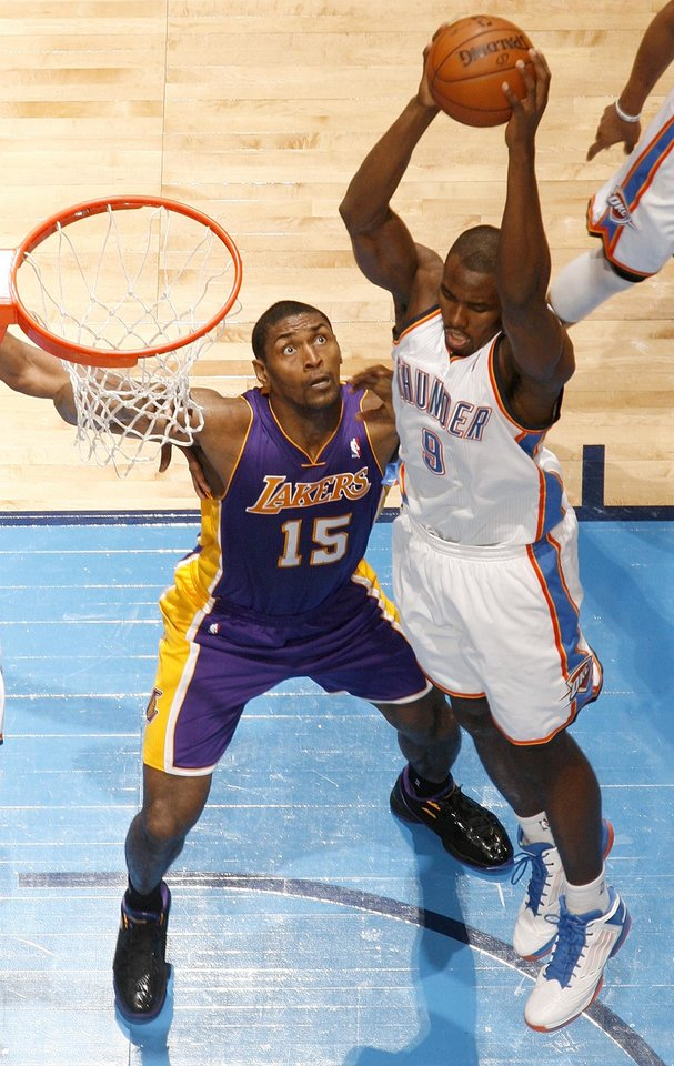Oklahoma City's Serge Ibaka (9) grabs a rebound over Los Angeles' Metta World Peace (15) during an NBA basketball game between the Oklahoma City Thunder and the Los Angeles Lakers at Chesapeake Energy Arena in Oklahoma City, Friday, Dec. 7, 2012. Oklahoma City won, 114-108. Photo by Nate Billings, The Oklahoman