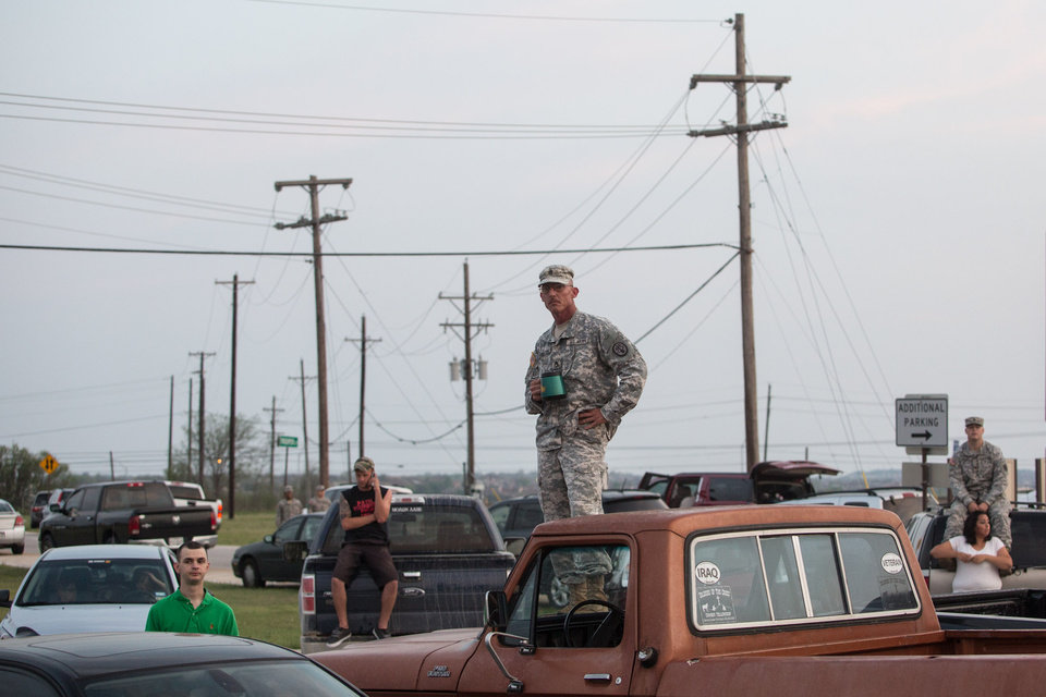 Photo - Military personnel and civilians wait in a parking lot outside of the Fort Hood military base for updates about the shooting that occurred inside on Wednesday, April 2, 2014, in Fort Hood, Texas. (AP Photo/Tamir Kalifa)