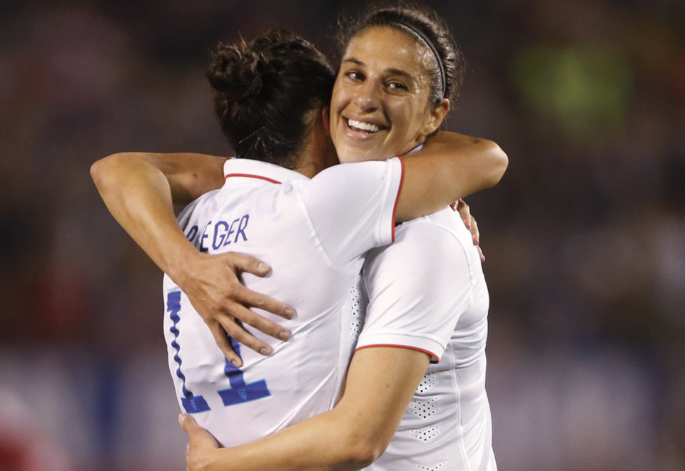 Photo - U.S. midfielder Carli Lloyd, right, hugs teammate Ali Krieger after scoring against China during the first half of an international friendly soccer match Thursday, April 10, 2014, in San Diego. (AP Photo/Lenny Ignelzi)