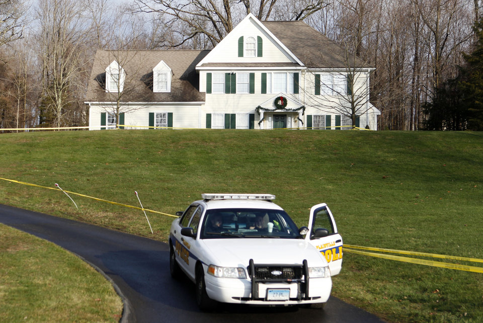 Photo - A police cruiser sits in the driveway as crime scene tape surrounds the home of Nancy Lanza, Tuesday, Dec. 18, 2012, in Newtown, Conn.  Nancy Lanza was killed by her son Adam Lanza before he forced his way into Sandy Hook Elementary School in Newtown Friday and opened fire, killing many others, including 20 children. (AP Photo/Jason DeCrow)