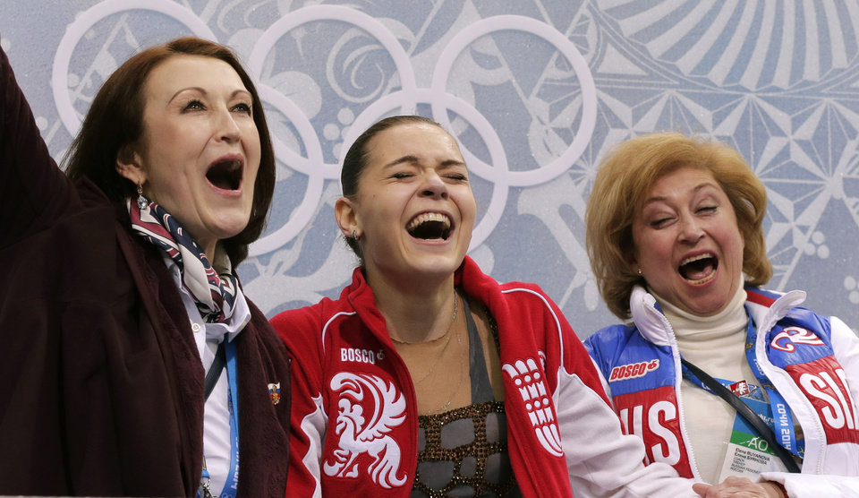 Photo - Adelina Sotnikova of Russia, centre, her coach Elena Buianova, right, and choreographer Irina Tagaeva react in the results area after she completed her routine in the women's free skate figure skating finals at the Iceberg Skating Palace during the 2014 Winter Olympics, Thursday, Feb. 20, 2014, in Sochi, Russia. (AP Photo/Bernat Armangue)