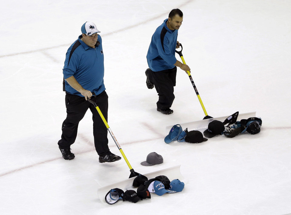 Photo - Workers gather hats thrown onto the ice by fans after San Jose Sharks' Martin Havlat's third goal of the NHL hockey game against the Colorado Avalanche, during the third period Friday, April 11, 2014, in San Jose, Calif. San Jose won 5-1. (AP Photo/Marcio Jose Sanchez)