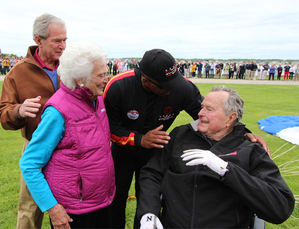 Photo - In this photo provided by the All Veteran Parachute Team, former President George H.W. Bush, right, is congratulated on his parachute jump by his son, former President George W. Bush, far left, his wife Barbara Bush and his tandem team partner Mike Elliott on his 90th birthday in Kennebunkport, Maine, Thursday, June 12, 2014. (AP Photo/All Veteran Parachute Team, Kenneth Wasley)